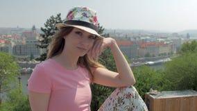 Η νέα γοητεία townswoman κάθεται στο λόφο ενάντια στο πανόραμα της πόλης στην ηλιόλουστη ημέρα φιλμ μικρού μήκους