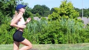 Η νέα γυναίκα η άσκηση του καρδιο workout Ελκυστική φίλαθλη γυναίκα που τρέχει στο πάρκο απόθεμα βίντεο