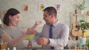 Η νέα γυναίκα έβαλε την ενίσχυση ακρόασης στο χαρούμενο άνδρα αυτιών φιλμ μικρού μήκους