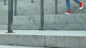 Η νέα γυναίκα έντυσε στα τζιν και τα αθλητικά παπούτσια που πηγαίνουν κάτω στα σκαλοπάτια, πόδια κοντά επάνω απόθεμα βίντεο
