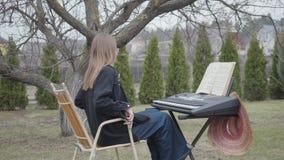 Η νέα γυναίκα έρχεται και κάθεται στο όργανο πληκτρολογίων υπαίθρια, προετοιμαμένος να παίξει Το σημειωματάριο με τις σημειώσεις  απόθεμα βίντεο