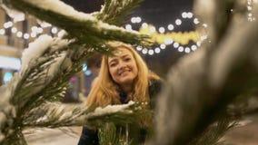 Η νέα γυναίκα έρχεται πιό κοντά κοιτάζοντας στη κάμερα Κλάδοι χριστουγεννιάτικων δέντρων στο χιόνι στο πρώτο πλάνο απόθεμα βίντεο