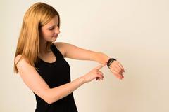 Η νέα γυναίκα αγγίζει το ρολόι της Apple Στοκ εικόνα με δικαίωμα ελεύθερης χρήσης