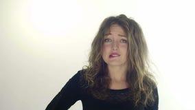 Η νέα γυναίκα δαγκώνει το χείλι της που ανησυχείται κάτι, φωτογραφία στούντιο που απομονώνεται σε ένα άσπρο υπόβαθρο φιλμ μικρού μήκους
