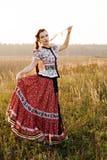 Η νέα γυναίκα αγροτών, έντυσε στο ουγγρικό εθνικό κοστούμι, που θέτει πέρα από το υπόβαθρο φύσης στοκ φωτογραφία με δικαίωμα ελεύθερης χρήσης