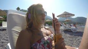 Η νέα γυναίκα ακούει μουσική και κρύο ποτό ποτών στην παραλία απόθεμα βίντεο