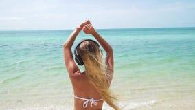 Η νέα γυναίκα ακούει μουσική στα ακουστικά στην παραλία απόθεμα βίντεο