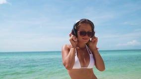 Η νέα γυναίκα ακούει μουσική στα ακουστικά στην παραλία φιλμ μικρού μήκους