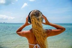 Η νέα γυναίκα ακούει μουσική στα ακουστικά στην παραλία Στοκ φωτογραφία με δικαίωμα ελεύθερης χρήσης