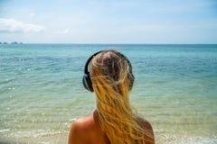Η νέα γυναίκα ακούει μουσική στα ακουστικά στην παραλία Στοκ Εικόνες