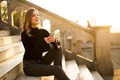 Η νέα γυναίκα ακούει τη μουσική από ένα κινητό τηλέφωνο έξω Στοκ εικόνα με δικαίωμα ελεύθερης χρήσης