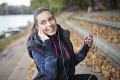 Η νέα γυναίκα ακούει τη μουσική από τον ποταμό στοκ φωτογραφία με δικαίωμα ελεύθερης χρήσης