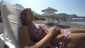 Η νέα γυναίκα ακούει τη μουσική στην παραλία απόθεμα βίντεο