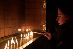 Η νέα γυναίκα ανάβει ένα κερί σε μια εκκλησία Στοκ φωτογραφία με δικαίωμα ελεύθερης χρήσης
