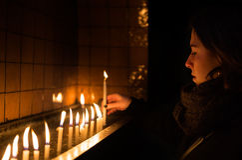 Η νέα γυναίκα ανάβει ένα κερί σε μια εκκλησία στοκ φωτογραφίες