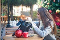 Η νέα γυναίκα ανοίγει την τσάντα της στον καφέ έξω Στοκ φωτογραφία με δικαίωμα ελεύθερης χρήσης