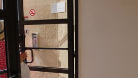 Η νέα γυναίκα ανοίγει τη πίσω πόρτα που φορά το κόκκινο φόρεμα και ένα καπέλο Πίσω πόρτα ανοικτή από μέσα