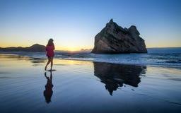 Η νέα γυναίκα απολαμβάνει την παραλία wharariki στη Νέα Ζηλανδία στοκ φωτογραφίες
