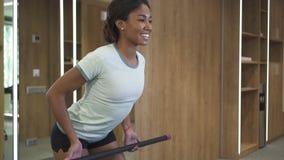 Η νέα γυναίκα ασκεί και ασκεί χρησιμοποιώντας τον ειδικό εξοπλισμό στη γυμναστική φιλμ μικρού μήκους