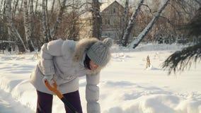 Η νέα γυναίκα αφαιρεί το χιόνι από το φτυάρι στα προάστια το χειμώνα φιλμ μικρού μήκους