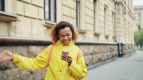 Η νέα γυναίκα αφροαμερικάνων ακούει τη μουσική μέσω των ακουστικών και το περπάτημα χορού κατά μήκος της οδού στη σύγχρονη πόλη απόθεμα βίντεο