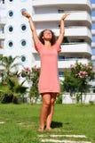 Η νέα γυναίκα αύξησε τα χέρια της απολαμβάνοντας τον ήλιο στοκ φωτογραφία με δικαίωμα ελεύθερης χρήσης