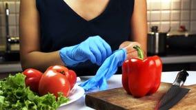 Η νέα γυναίκα βάζει στα μπλε γάντια, που στέκονται στην κουζίνα του σπιτιού φιλμ μικρού μήκους