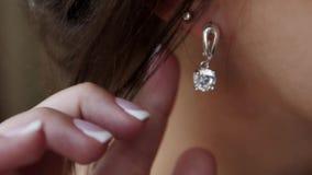 Η νέα γυναίκα βάζει στα όμορφα σκουλαρίκια απόθεμα βίντεο