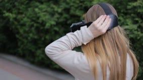 Η νέα γυναίκα βάζει στην κάσκα εικονικής πραγματικότητας απόθεμα βίντεο