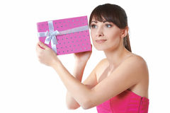 Η νέα γυναίκα βάζει το αυτί της στο κιβώτιο δώρων Στοκ Εικόνες