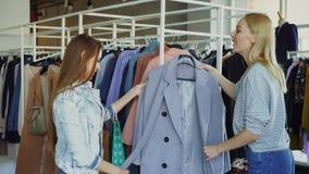 Η νέα γυναίκα βοηθά το φίλο της για να βρεί το παλτό Φέρνει το νέο μοντέλο της, την αφήγηση για το και την παρουσίασή της απόθεμα βίντεο