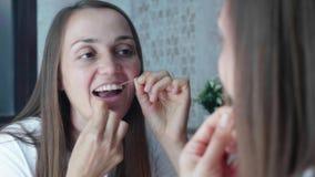 Η νέα γυναίκα βουρτσίζει τα δόντια με το οδοντικό νήμα στο λουτρό, αντανάκλαση καθρεφτών απόθεμα βίντεο
