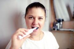 Η νέα γυναίκα βουρτσίζει τα δόντια στο λουτρό μια ηλεκτρική βούρτσα Στοκ φωτογραφία με δικαίωμα ελεύθερης χρήσης