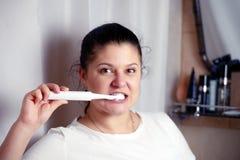 Η νέα γυναίκα βουρτσίζει τα δόντια στο λουτρό μια ηλεκτρική βούρτσα Στοκ Εικόνες