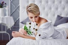 Η νέα γυναίκα βρίσκεται σε ένα κρεβάτι με μια ανθοδέσμη των camomiles στοκ εικόνα