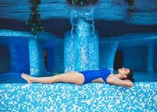 Η νέα γυναίκα βρίσκεται στην άκρη της λίμνης με το νερό εσωτερικό swimpool aquapark χαριτωμένο πάρκο νερού πισινών κοριτσιών πλησ Στοκ Φωτογραφία
