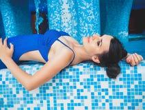 Η νέα γυναίκα βρίσκεται στην άκρη της λίμνης με το νερό εσωτερικό swimpool aquapark χαριτωμένο πάρκο νερού πισινών κοριτσιών πλησ Στοκ Φωτογραφίες