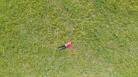 Η νέα γυναίκα βρίσκεται στη χλόη στα κίτρινα χρώματα Τοπ άποψη από το ύψος απόθεμα βίντεο