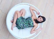 Η νέα γυναίκα βρίσκεται στο μόνιππο -μόνιππο-longue κύκλων Στοκ Φωτογραφία