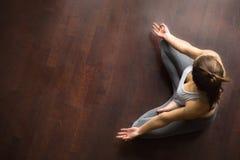 Η νέα γυναίκα γιόγκη στο μισό Lotus θέτει, υψηλή άποψη γωνίας Στοκ Εικόνες