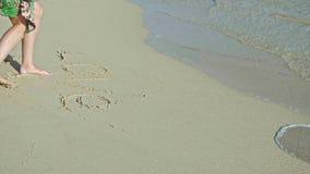 Η νέα γυναίκα γράφει την αγάπη στην άμμο θάλασσας Ξέβγαλμα με το θαλάσσιο νερό, καραϊβική θάλασσα, απόθεμα βίντεο