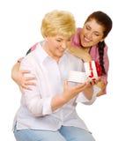 Η νέα γυναίκα δίνει το δώρο στη μητέρα της στοκ φωτογραφία