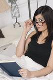 Η νέα γυναίκα διαβάζει στα γυαλιά ανάγνωσης εκμετάλλευσης σπορείων Στοκ εικόνες με δικαίωμα ελεύθερης χρήσης