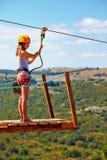 Η νέα γυναίκα είναι έτοιμη να κατεβεί στο zipline στο βουνό, ακραίος αθλητισμός Στοκ Εικόνα