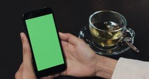 Η νέα γυναίκα είναι εκμετάλλευση Smartphone με την πράσινη οθόνη στον άνετο καφέ περιστασιακός τρόπος ζωή&si απόθεμα βίντεο