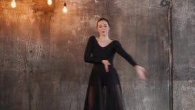 Η νέα γυναίκα είναι κομψός χορός χορού σε ένα σκοτεινό δωμάτιο, που κινεί τα χέρια απόθεμα βίντεο