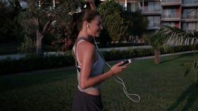 Η νέα γυναίκα είναι χορός, κρατώντας το smartphone στην πράσινη χλόη το καλοκαίρι υπαίθρια απόθεμα βίντεο