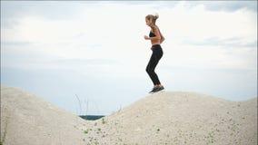 Η νέα γυναίκα εκπαιδεύει ενεργά στους αθλητικούς ανταγωνισμούς που τρέχει κατά μήκος του αμμώδους πάρκου απόθεμα βίντεο