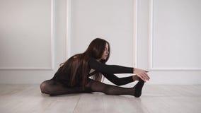 Η νέα γυναίκα εκπαιδεύει την ευελιξία των ποδιών της σε μια κατηγορία χορού απόθεμα βίντεο