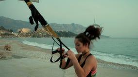 Η νέα γυναίκα εκτελεί την πηδώντας άσκηση αντίστασης αθλητικών ζωνών συνολική φιλμ μικρού μήκους